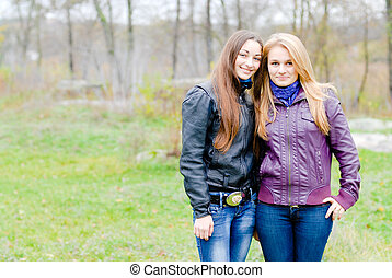 Two Teen Girl Friends Laughing in spring or autumn outdoors...