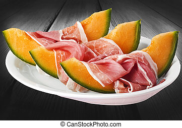 Ham and melon on the white dish