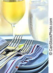 Plates and cutlery - Table setting with stack of plates and...