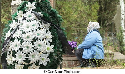 Family Member At The Cemetery - Elderly woman at the grave...