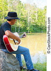 Guitar Player at the Pond - a man in a cowboy hat plays an...