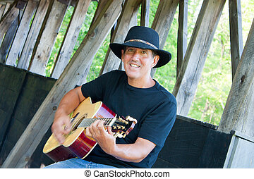 Country Musician - A man in jeans and cowboy hat plays...