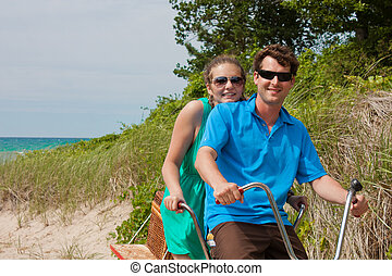 bicycle built for two - A young couple at the beach sand...