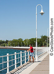 boardwalk at Sarnia Bay vertical - A man stands looking out...