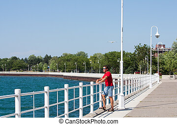 boardwalk at Sarnia Bay horizontal - A man stands looking...
