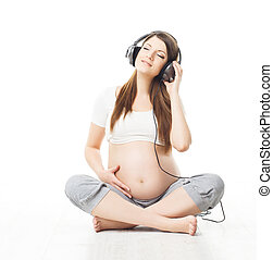 Pregnant woman listening to music in headphones and relaxing