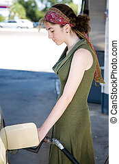 Teen Pumping Gas - Teen girl pumping gas into the tank of...
