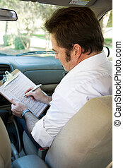 Driving Test Checklist - Instructor marks checklist during a...