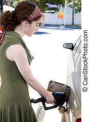 Filling the Tank - Young woman filling the gas tank of her...