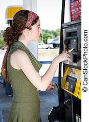 Paying For Gas - Young woman uses her ATM card to pay for...