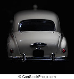 White vintage car rear view in darkness