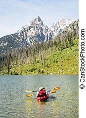 Kayaking in the Mountains - A senior couple kayaking on a...