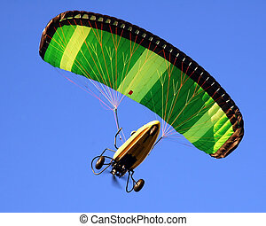 Paragliding - Under-view of a bright yellow and green...