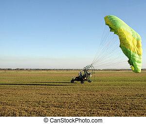 Paraglider Landing - A paraglider landing on flatland.