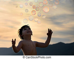 Boy with bubbles - Little boy trying to catch some soap...