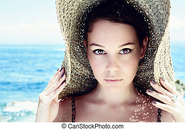 beautiful woman - Young, beautiful woman wearing a straw hat...
