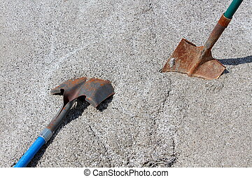 Two shovels in pile of sand - Two well worn work shovels in...