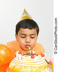 kid blowing candle on birthday cake - an asian kid blowing...