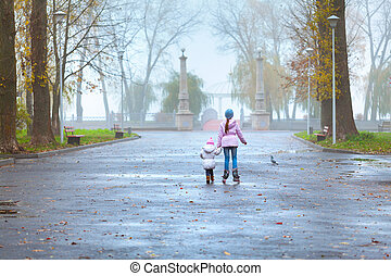 Two sisters walking in the autumn park