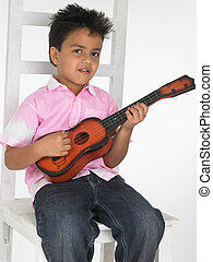 boy playing a toy guitar - an adorable asian boy playing a...