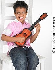 asian boy playing a toy guitar - an adorable asian boy...