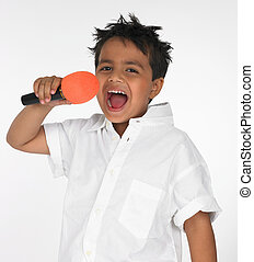 boy singing into his mike - a cute asian Indian boy of...