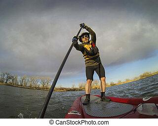 paddling stand up board - mature male paddler enjoying...