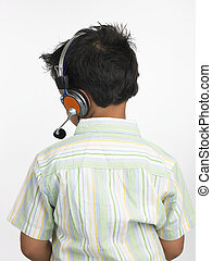 boy of indian origin with headphone - back profile of an...
