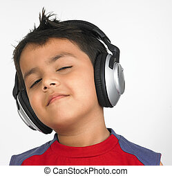 a cute kid listening to music - an adorable asian boy of...
