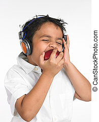 boy eating and l istening to music - an adorable asian boy...