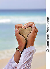 Heart from sand in hands of the woman on a background of the...