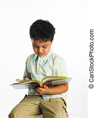 boy reading a book - a handsome Asian boy of indian origin...