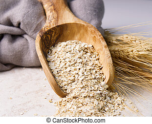 Rolled Oats in Wooden Spoon - Horizontal photo of rolled...