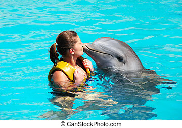 I love dolphins - A picture of a young woman kissing a...