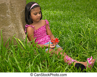 child in a park playing with flower