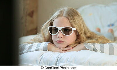 Little Girl Watching 3D TV at Home - Little blond girl...