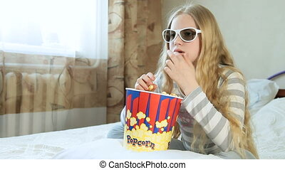 Child Watching 3D Movie at Home - Little blonde girl eating...