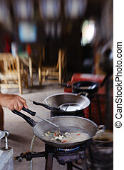 A chef or cook is preparing multiple dishes. Thai outdoor food.