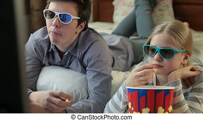 Watching 3D TV Movie at Home - Brother and sister eating...