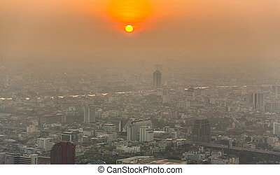 View across Bangkok skyline showing in sunset with smog and...