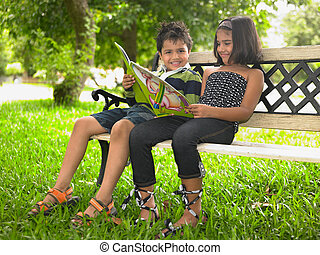kids reading a book in a park - Asian kids reading a book in...