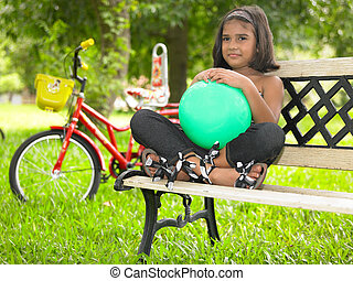 kid sitting on a bench in a park