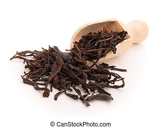 dry black tea leaves on the wooden spoon, on white...