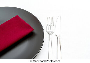 Black plate with cutlery and red napkin