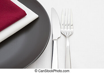 Black plate with cutlery with red and white napkins