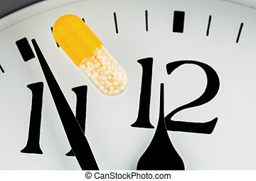 capsule on a clock, symbolic photo for healthcare, health...