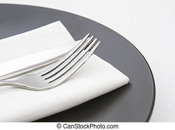 Cutlery on white napkin with plate