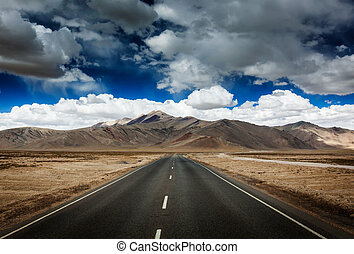 Road on plains in Himalayas with mountains - Travel forward...