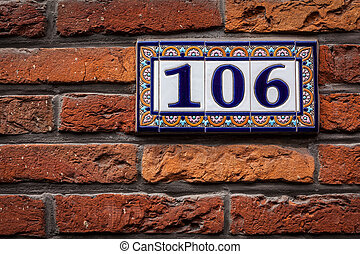 Decorated house number on brick wall in Europe. Bruges...