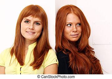 Two young beautiful redhead women